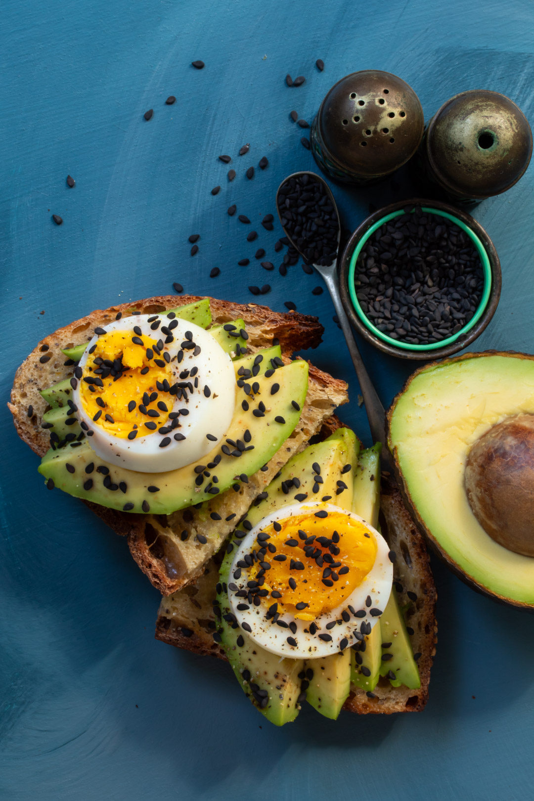 avocado toasts with hard boiled eggs blue background