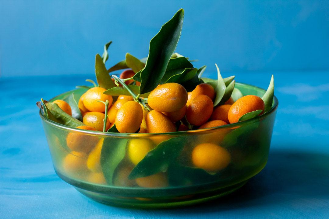cumquats in green glass bowl