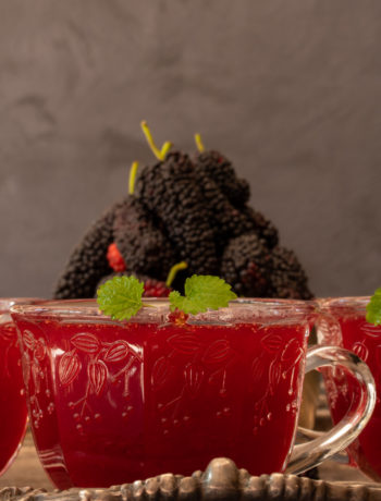 spiced mulberry shrub with mulberries in background