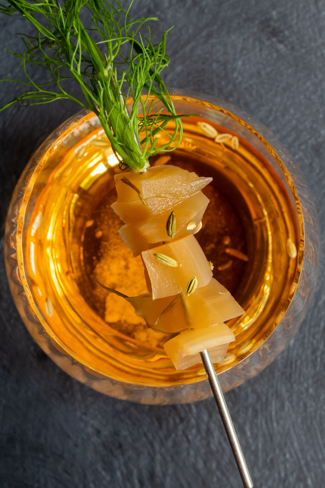 fennel pickle old fashioned cocktail: from above with line of drink pick