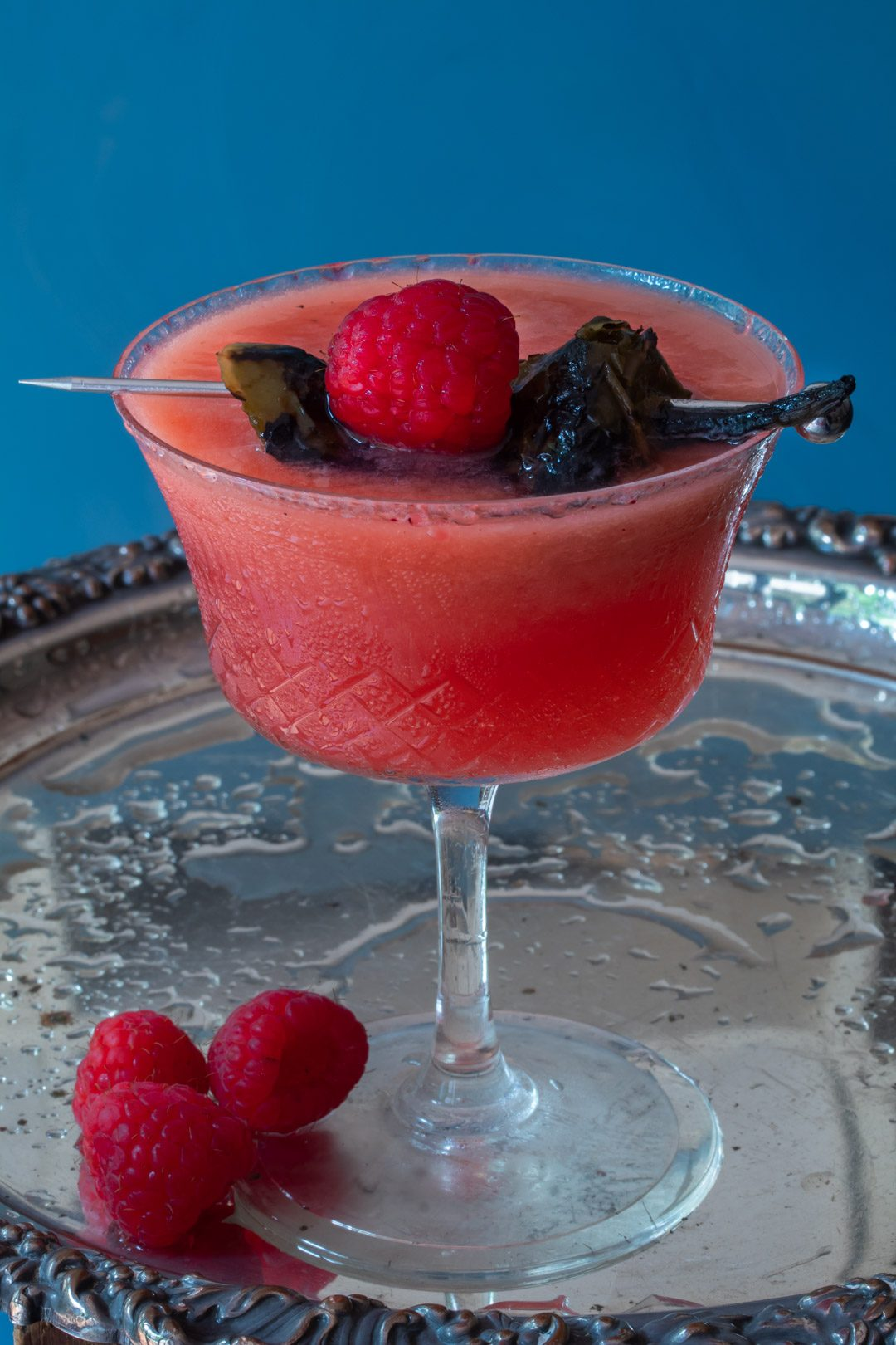Pickled jalapeno and raspberry margarita cocktail with hibiscus sugar: on silver tray