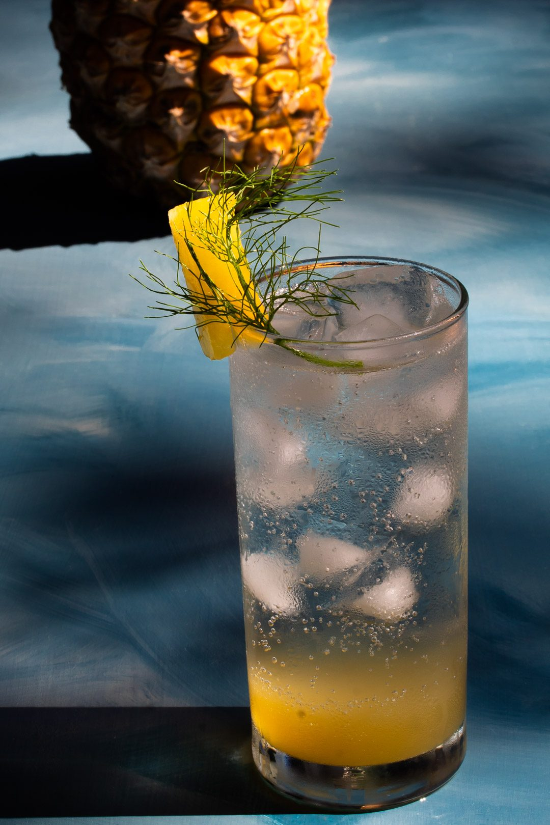 pineapple fennel shrub syrup from a 45 degree angle with pineapple in the background