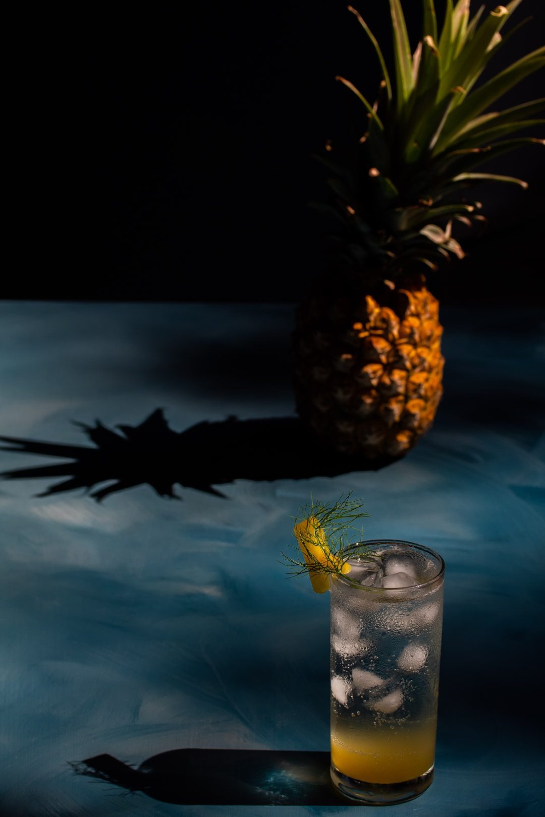 pineapple fennel shrub syrup from 45 degrees with pineapple and shadow in background