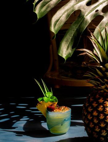 Pickle Mai Tai cocktail framed by shadows from a pineapple and monstera leaf