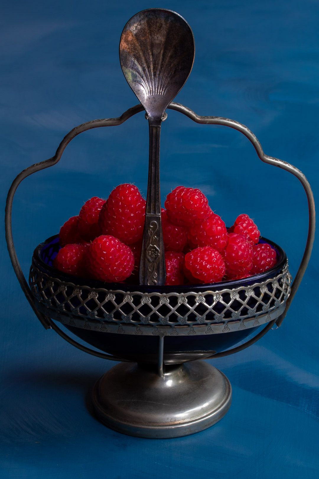 Making Raspberry shrub syrup drinking vinegar with raspberries in vintage blue glass sugar bowl with spoon centre
