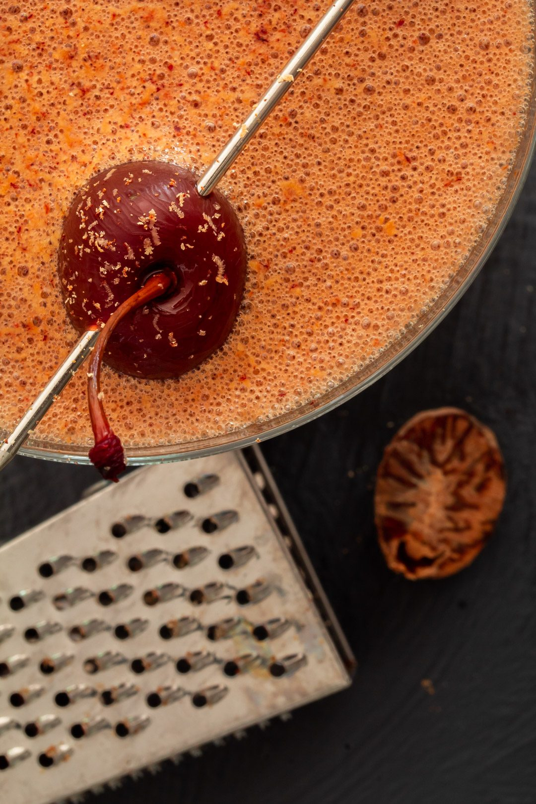 pickled cherry chocolate sherry flip cocktail from above with nutmeg and grater
