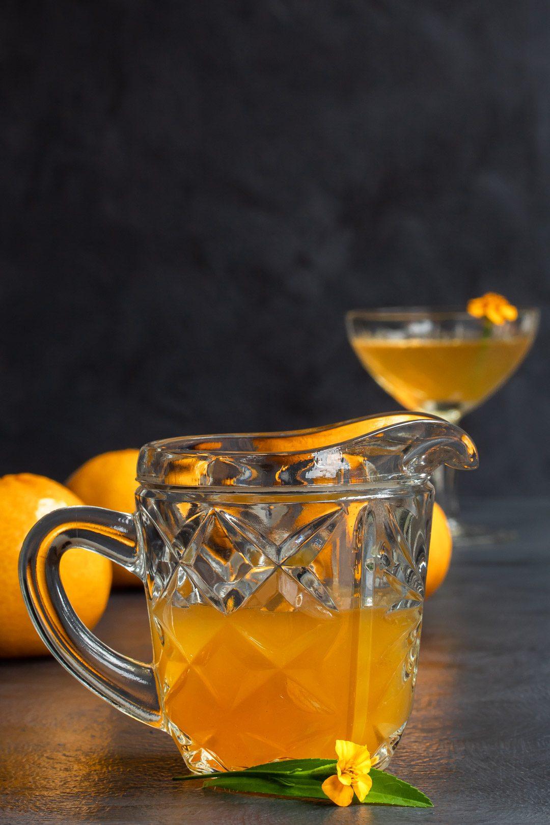 Mandarin tarragon shrub syrup drinking vinegar in vintage glass jug with cocktail in background