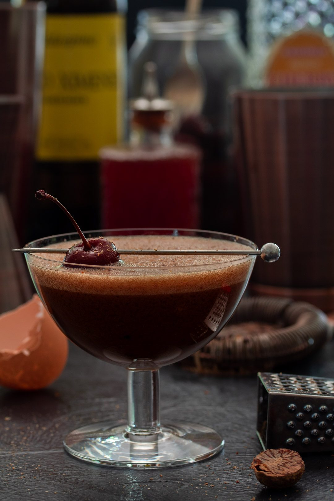 Pickled cherry chocolate sherry flip cocktail with bottles in background