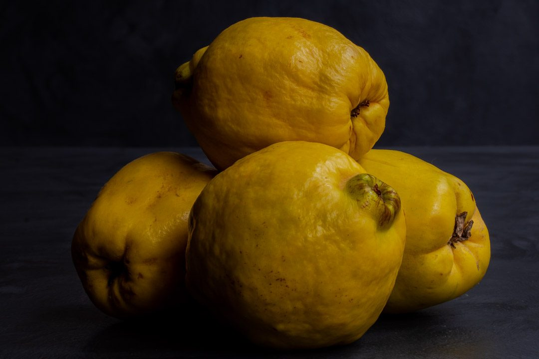 Making Vintage Quince Cordial with quinces in pile
