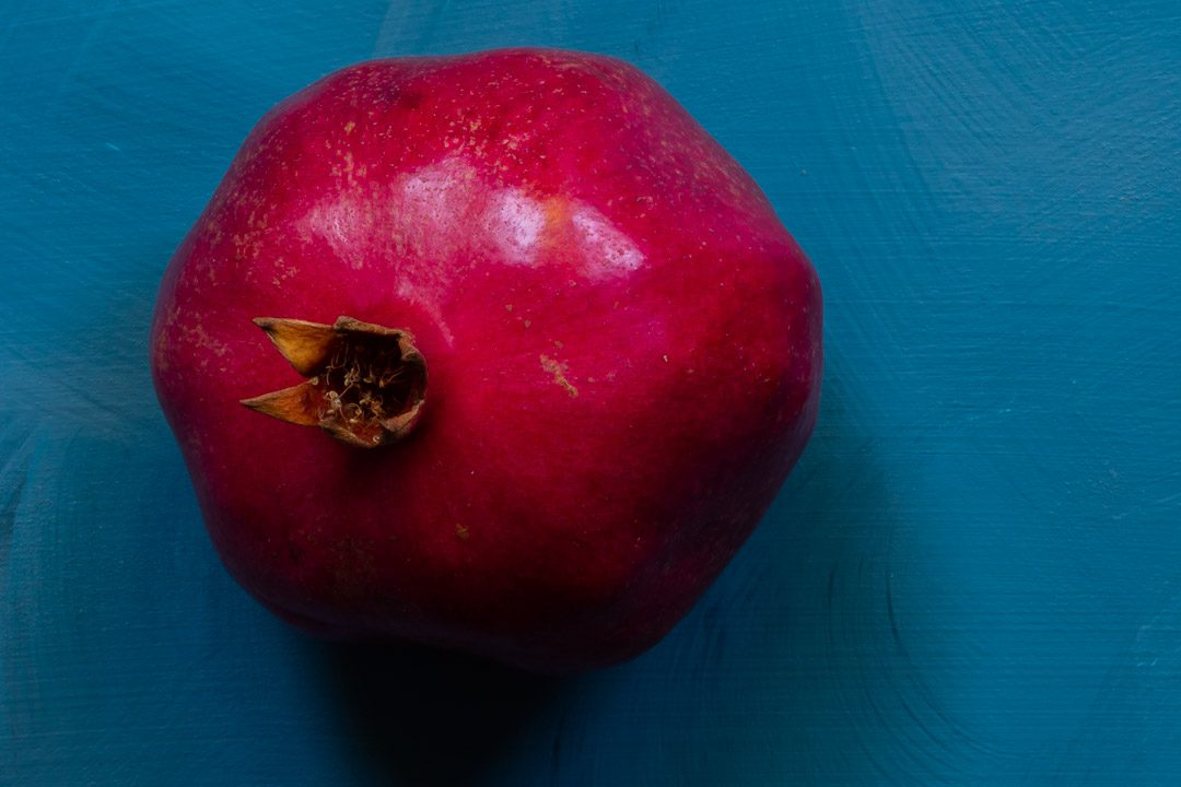 pomegranate on blue background from above used to make grenadine