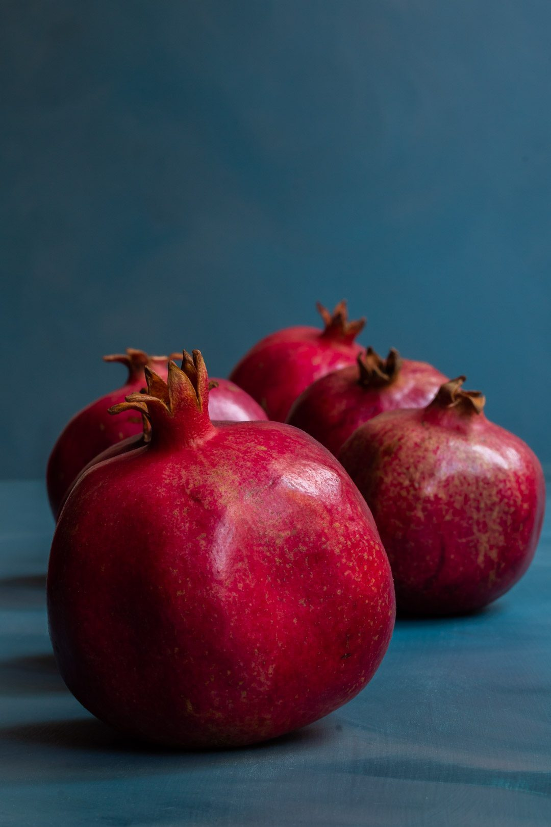 pomegranates in a row on blue background used to make grenadine
