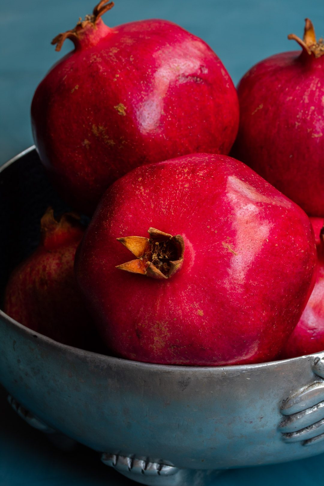 pomegranates in metal bowl from 45 degrees used to make grenadine