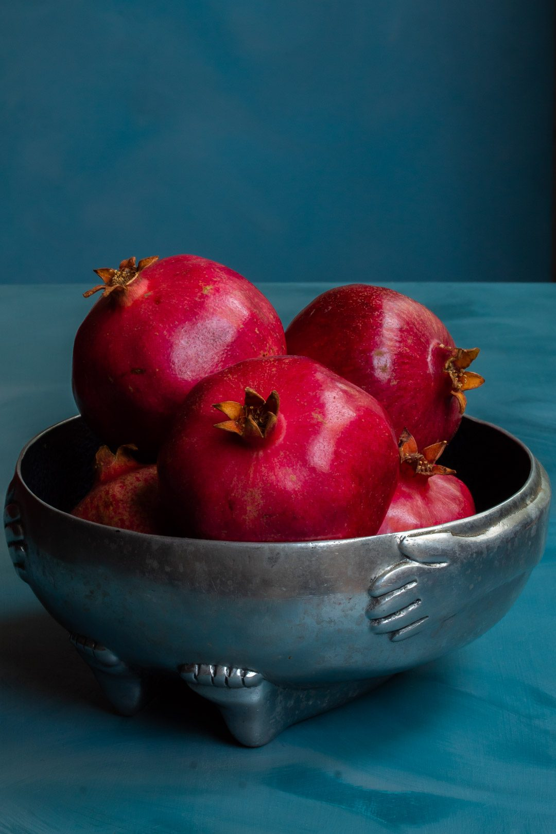 pomegranates in metal bowl used to make grenadine on blue background