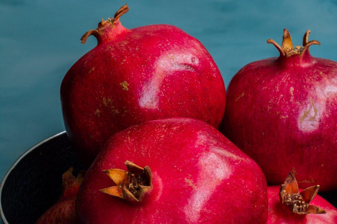 pomegranates in metal bowl close up used to make grenadine