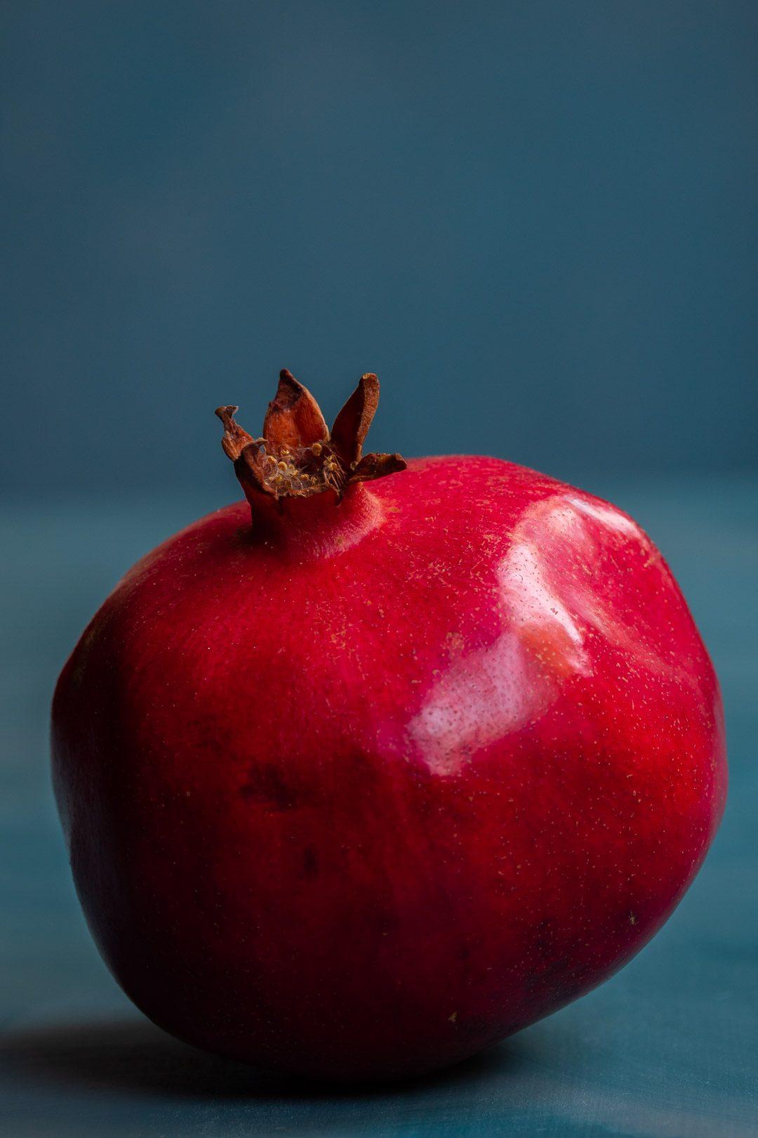 pomegranate solo on blue background used to make grenadine