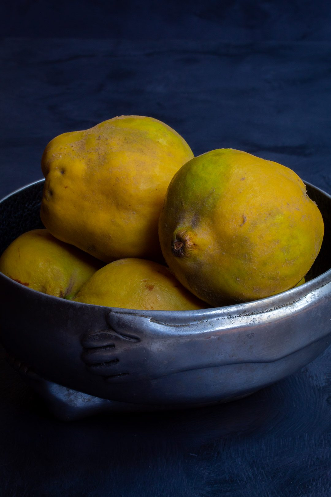 Making spiced pickled quinces with quinces in metal bowl on grey background