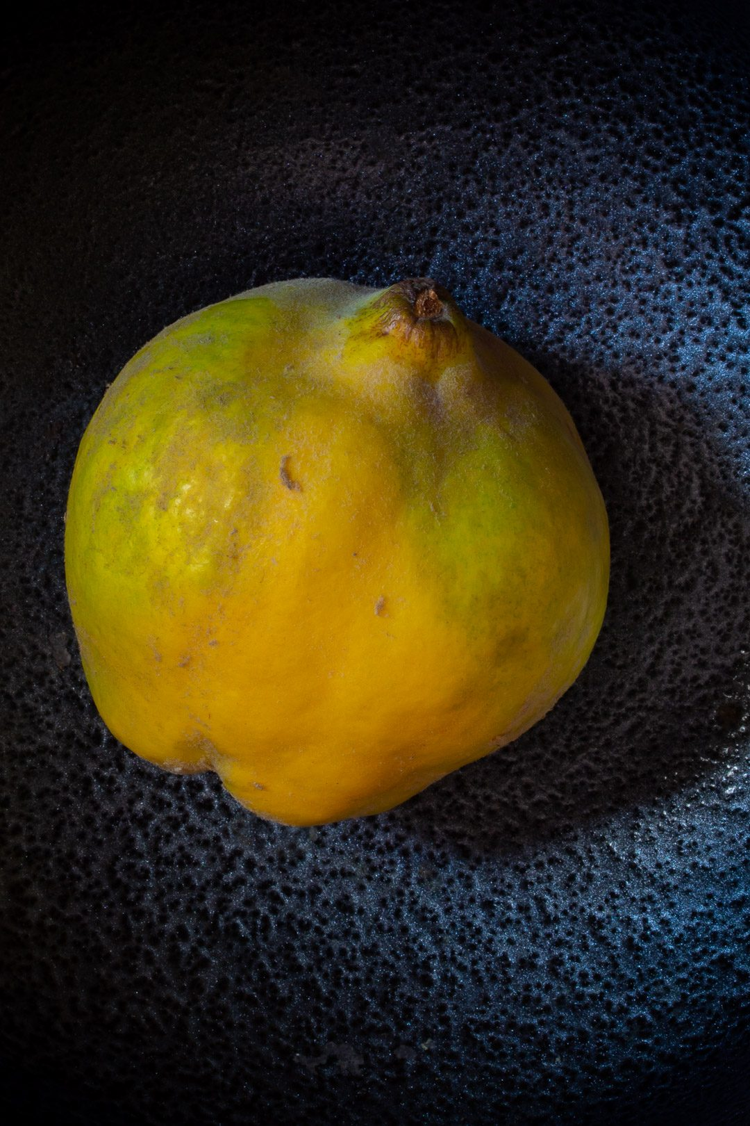 Making Spiced pickled quinces with single quince on black metallic background