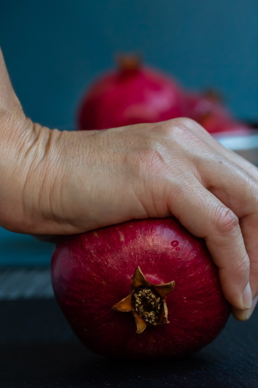 rolling a pomegranate by hand to split the membranes and free the seeds to make grenadine