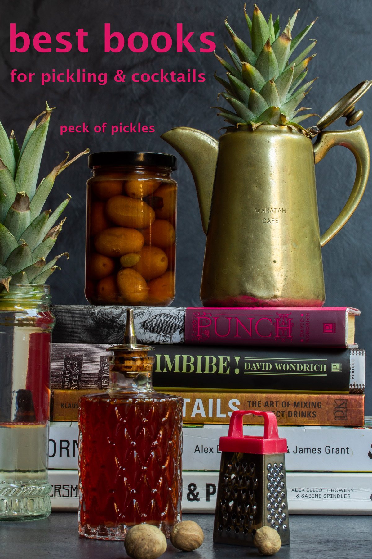 pickling and cocktail books with pickles, bitters, pineapple plants, nutmeg grater