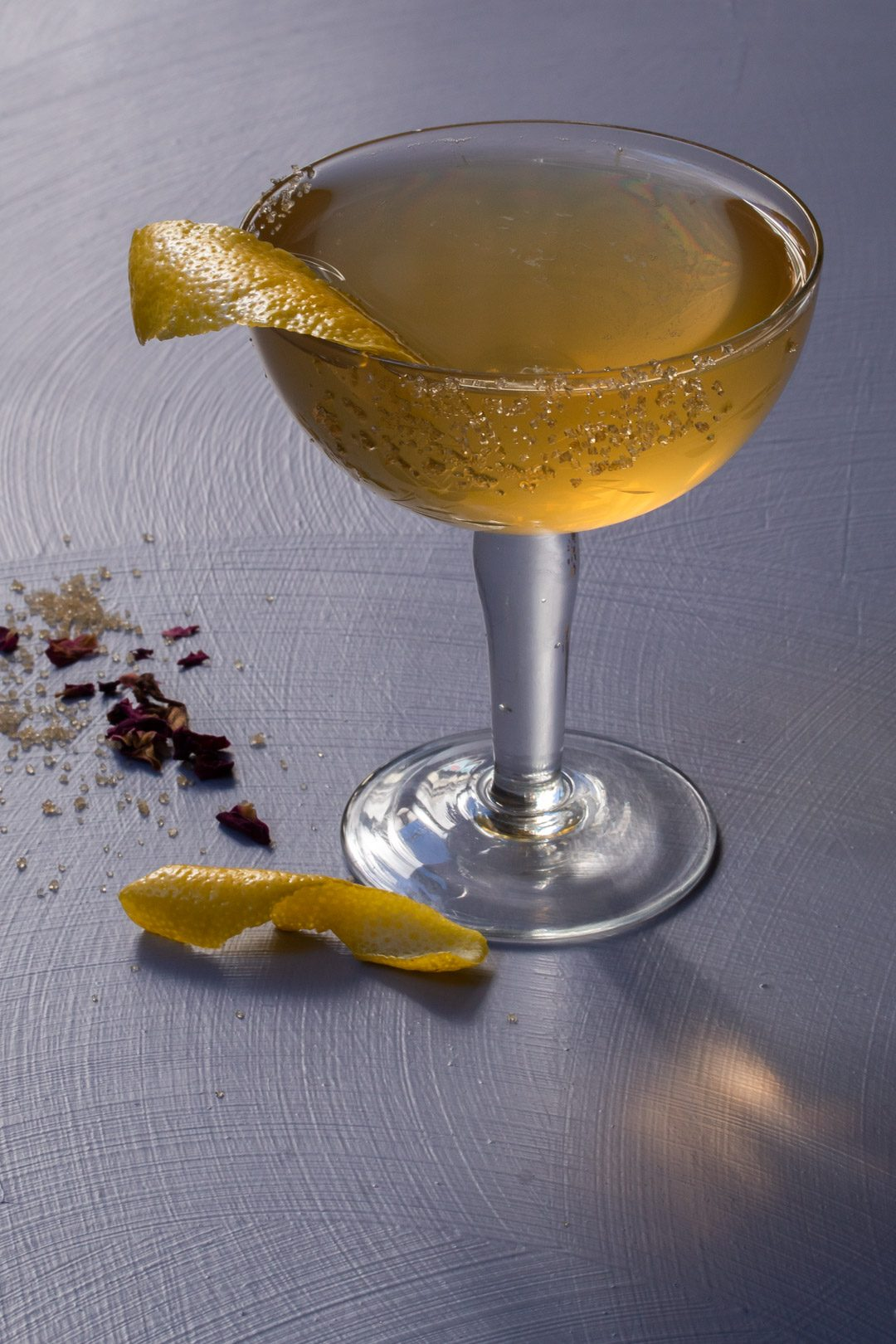 Fancy quince brandy champagne cocktail from 45 degrees on light purple background