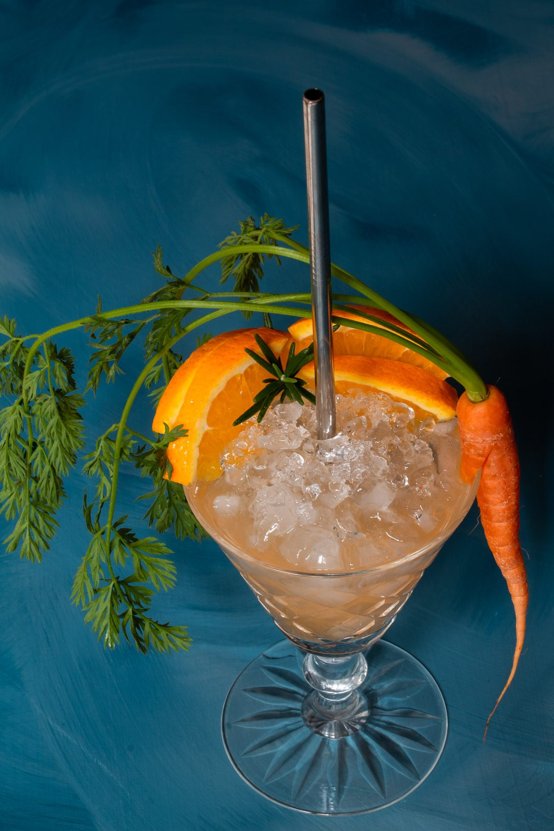 carrot shrub daisy cocktail from 45 degree angle on a blue textured background