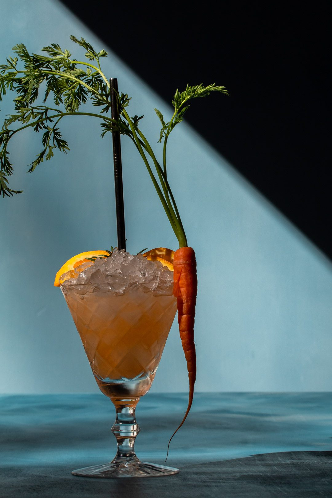 carrot shrub daisy cocktail with shadows to right on blue background