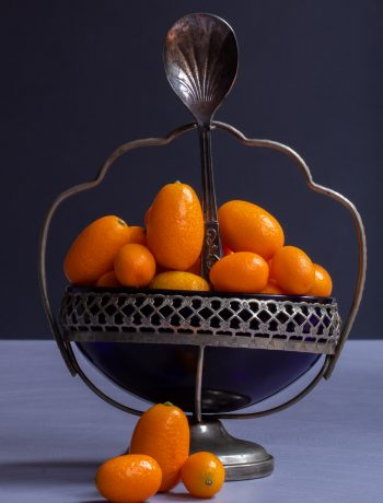 making cumquat brandy with cumquats in blue glass sugar bowl with 3 cumquats in foreground and sugar spoon on light purple and grey background