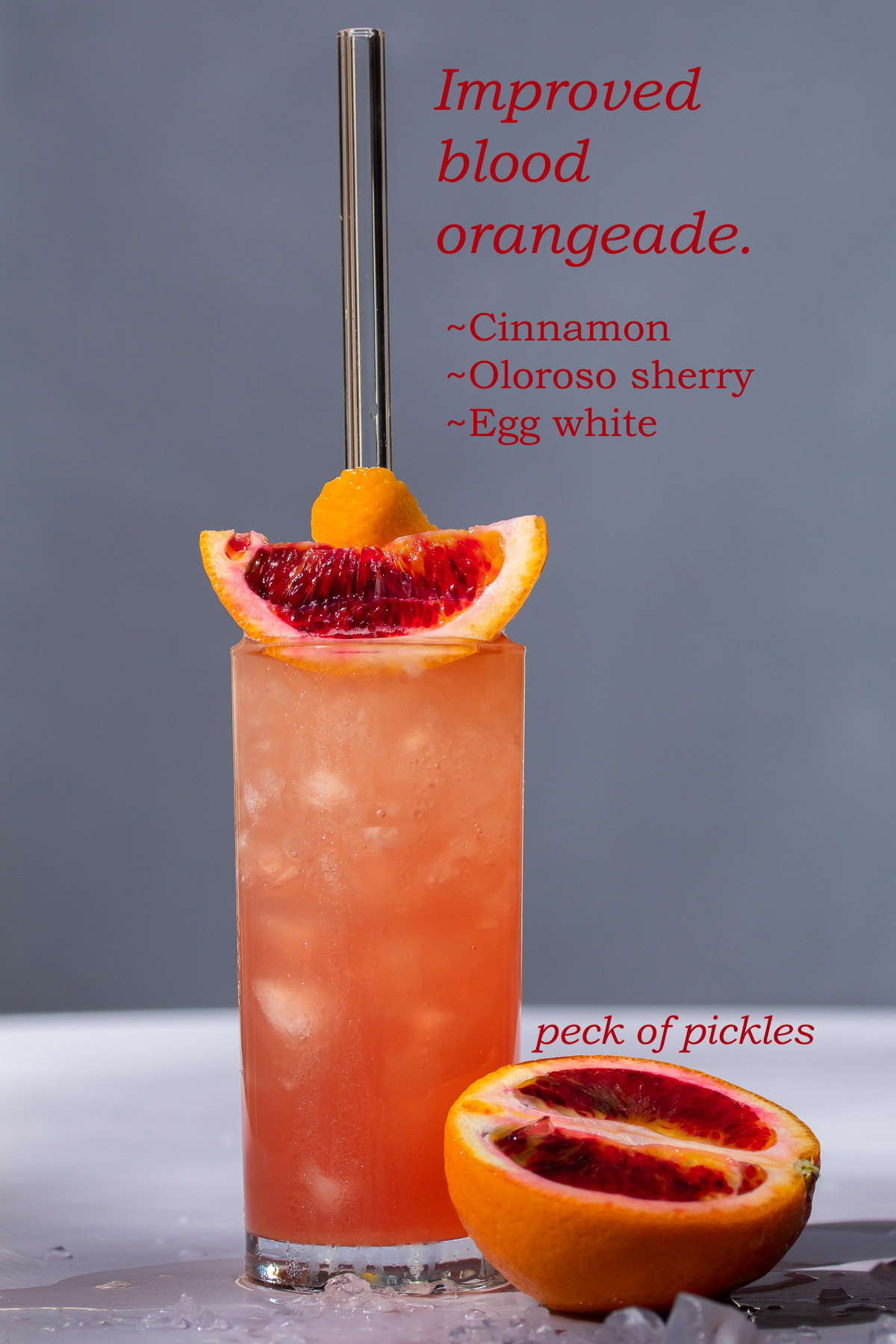 improved blood orangeade with blood orange on light purple and grey background