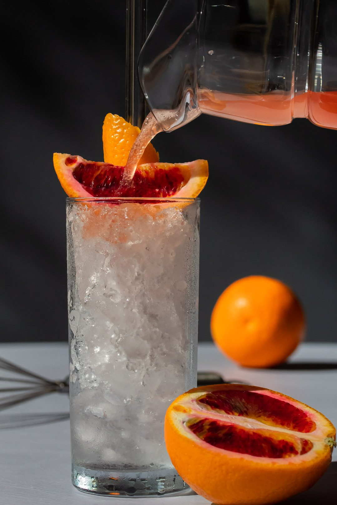 improved blood orangeade being poured into glass of crushed ice