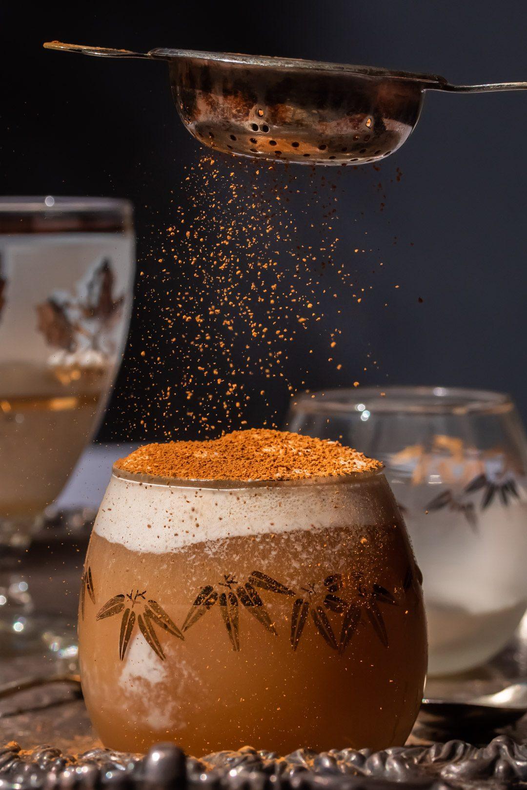 sprinkling cinnamon on lemon myrtle ginger beer spiders with vintage tea strainer