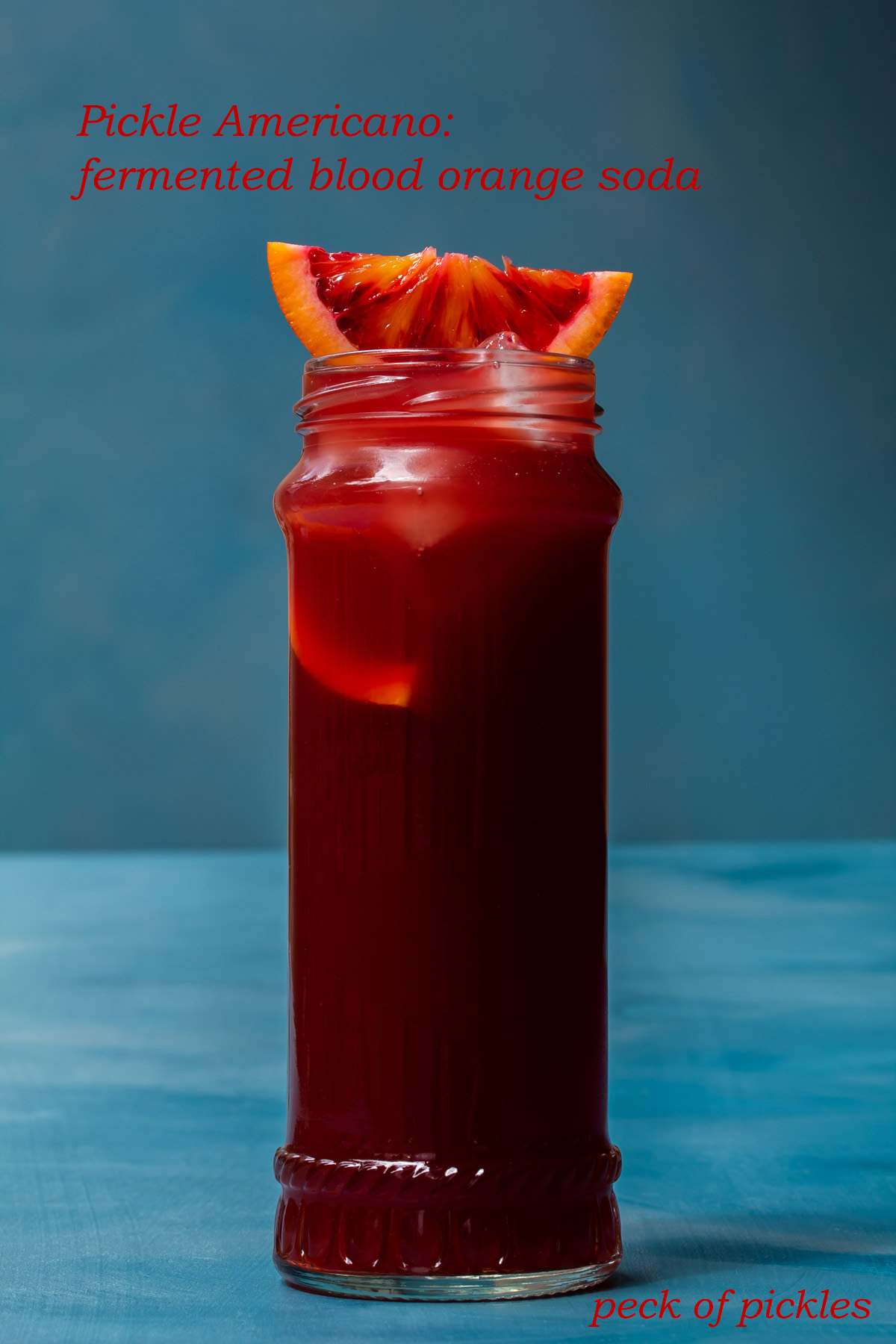 pickle blood orange Americano cocktail isolated on blue background