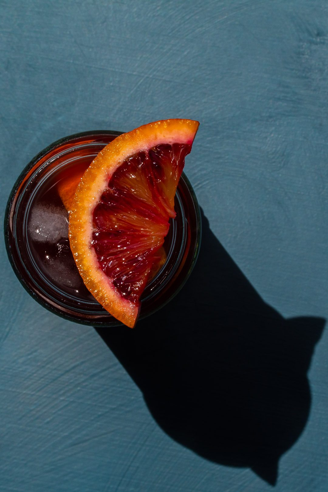 Pickle blood orange Americano cocktail from above on blue background with shadow