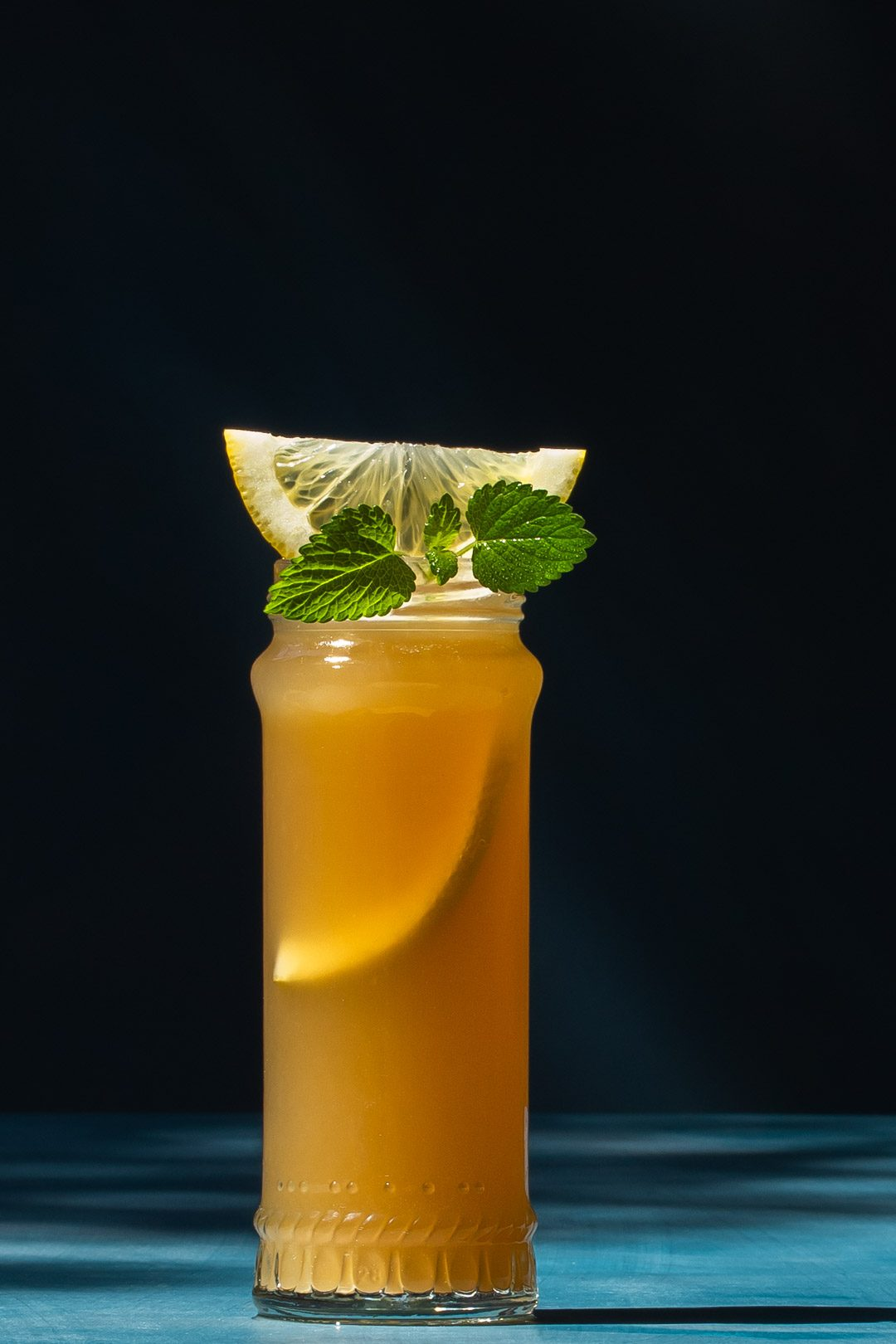 Pickle Gin Buck Cocktail on blue background to left with shadows