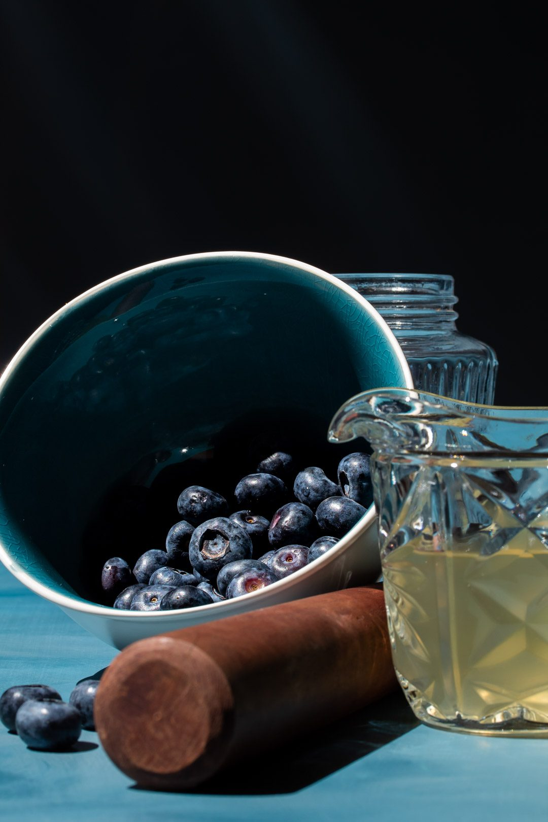 making blueberry shrub syrup with blue bowl of blueberries and cut glass vintage jug of coconut vinegar