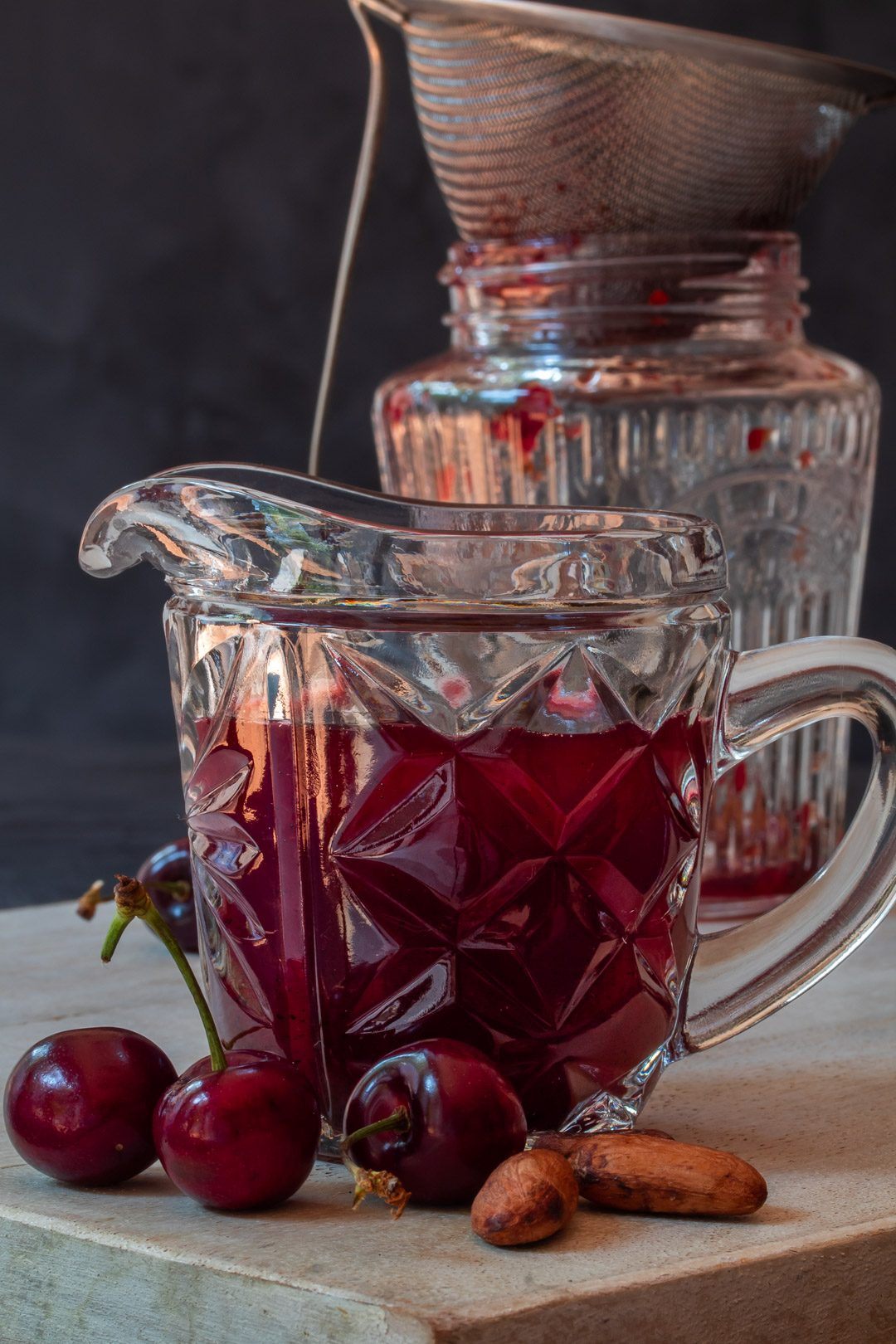 cherry shrub syrup in vintage cut glass jug for cherry shrub brandy daisy