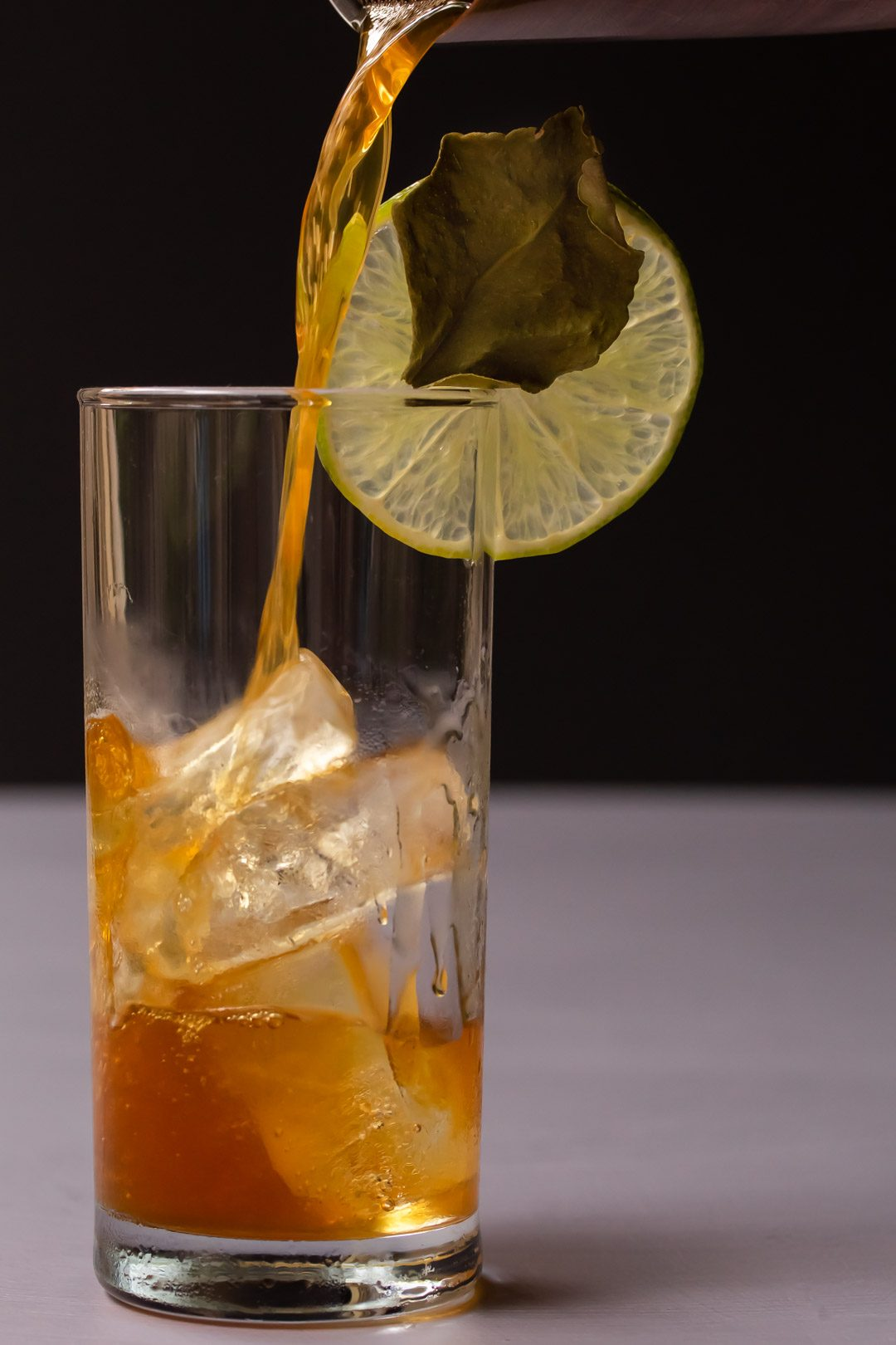pouring rum and lime for lime lightening dark 'n stormy glass part full