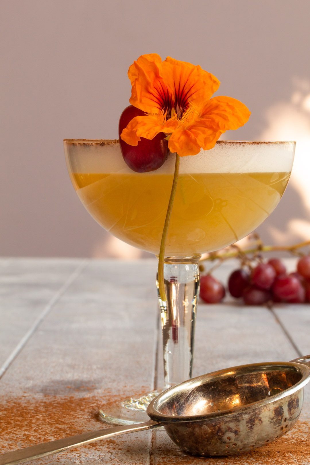 Autumn grape silver sour: with tea strainer and grapes in background
