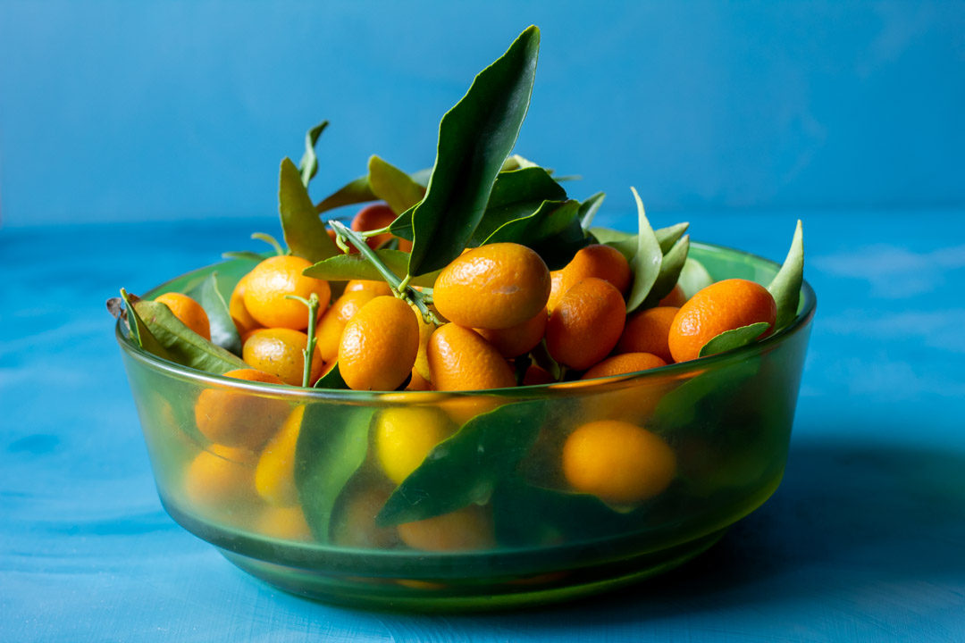 cumquats in green glass bowl