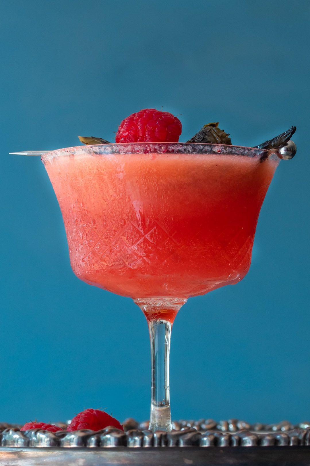 Pickled jalapeno and raspberry margarita cocktail with hibiscus sugar: blue background