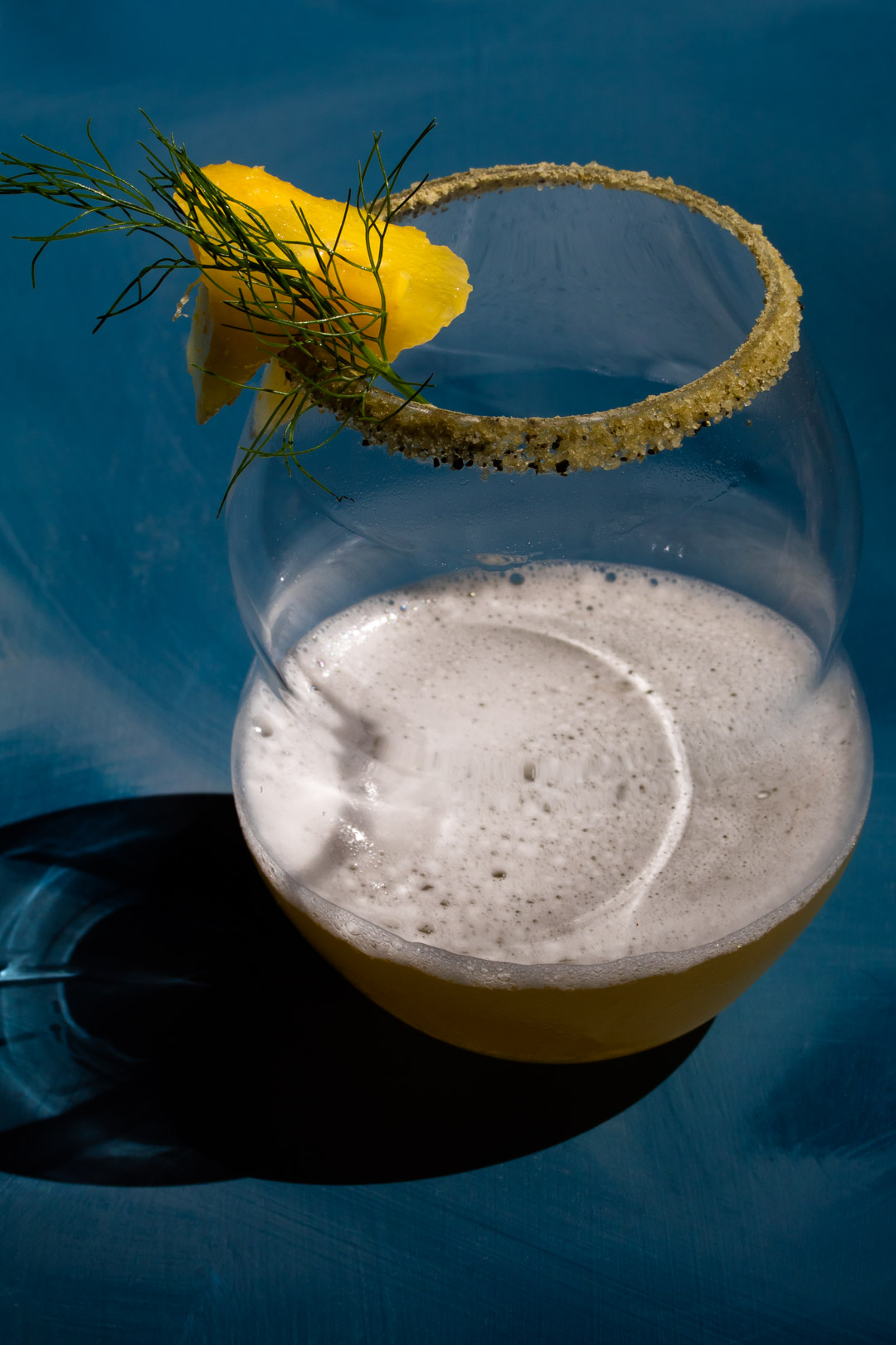 pineapple fennel shrub margarita cocktail isolated on blue background