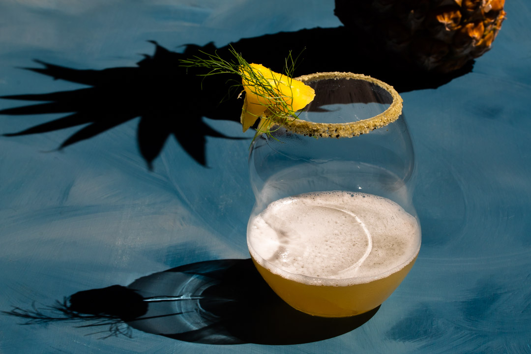 pineapple fennel shrub margarita cocktail with pineapple shadow framing glass