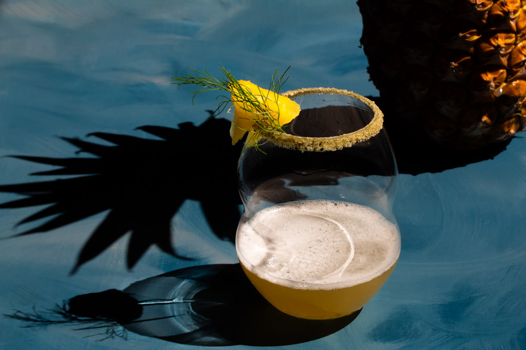 pineapple fennel shrub margarita cocktail with pineapple and shadow closely framing glass