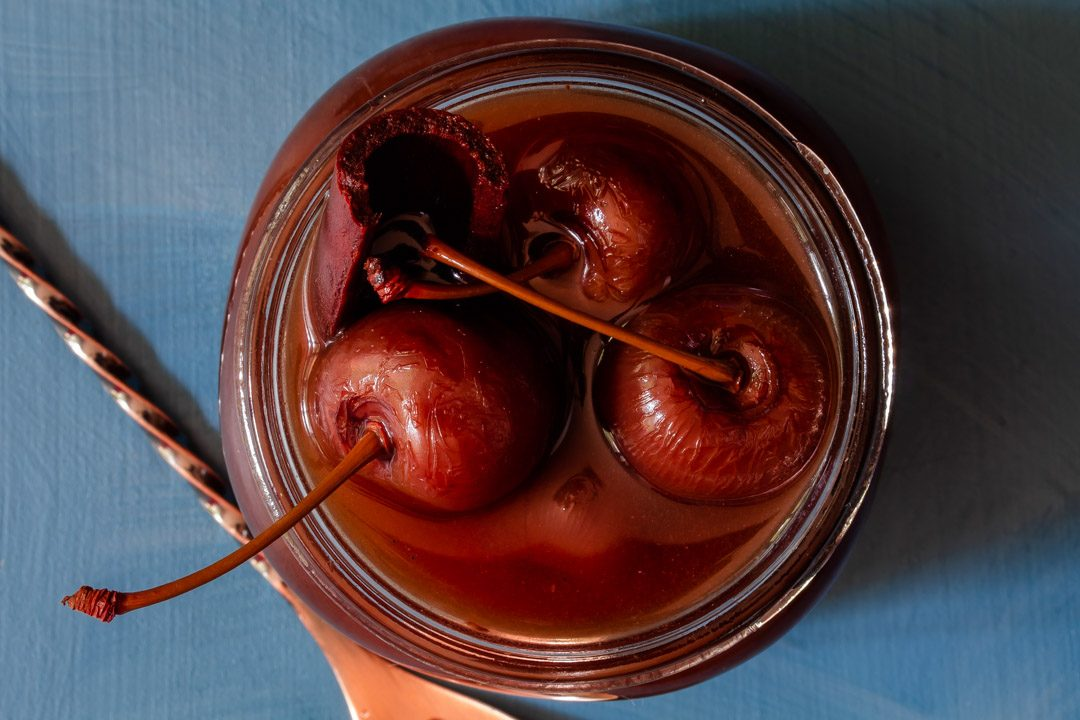 Spiced pickled cherries close up from above with bar spoon