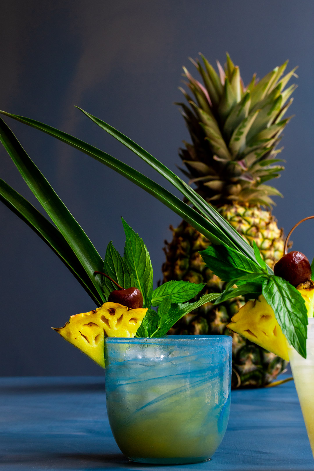 Pickle Mai Tai cocktail with blue glass front and pineapple in background