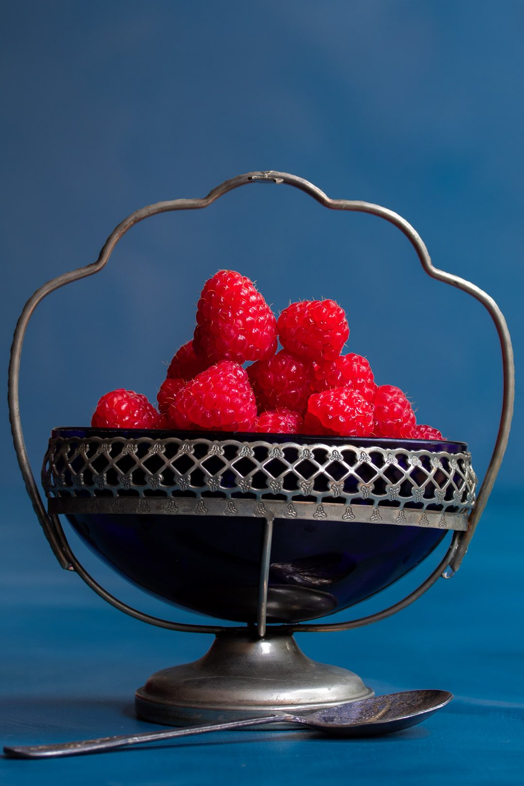 Making Raspberry shrub syrup drinking vinegar with raspberries in blue glass vintage sugar bowl