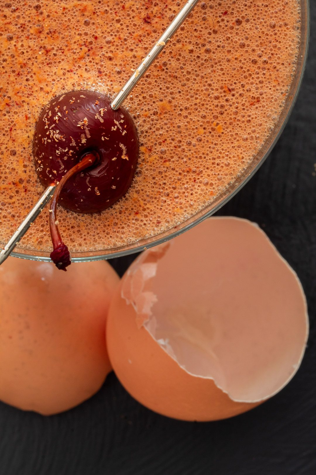 pickled cherry chocolate sherry flip cocktail from above with egg shell