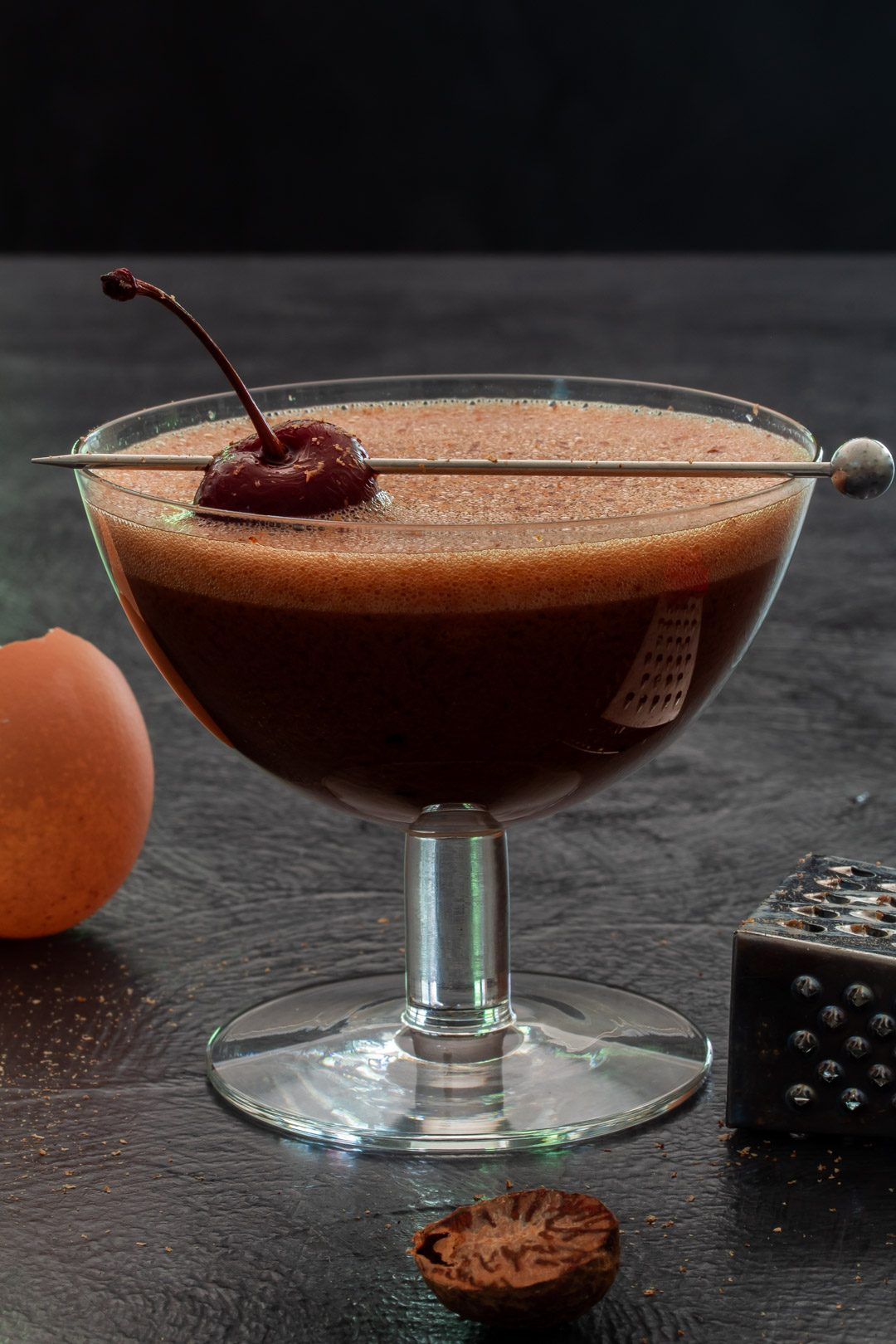 Pickled cherry chocolate sherry flip cocktail with egg shell and nutmeg grater