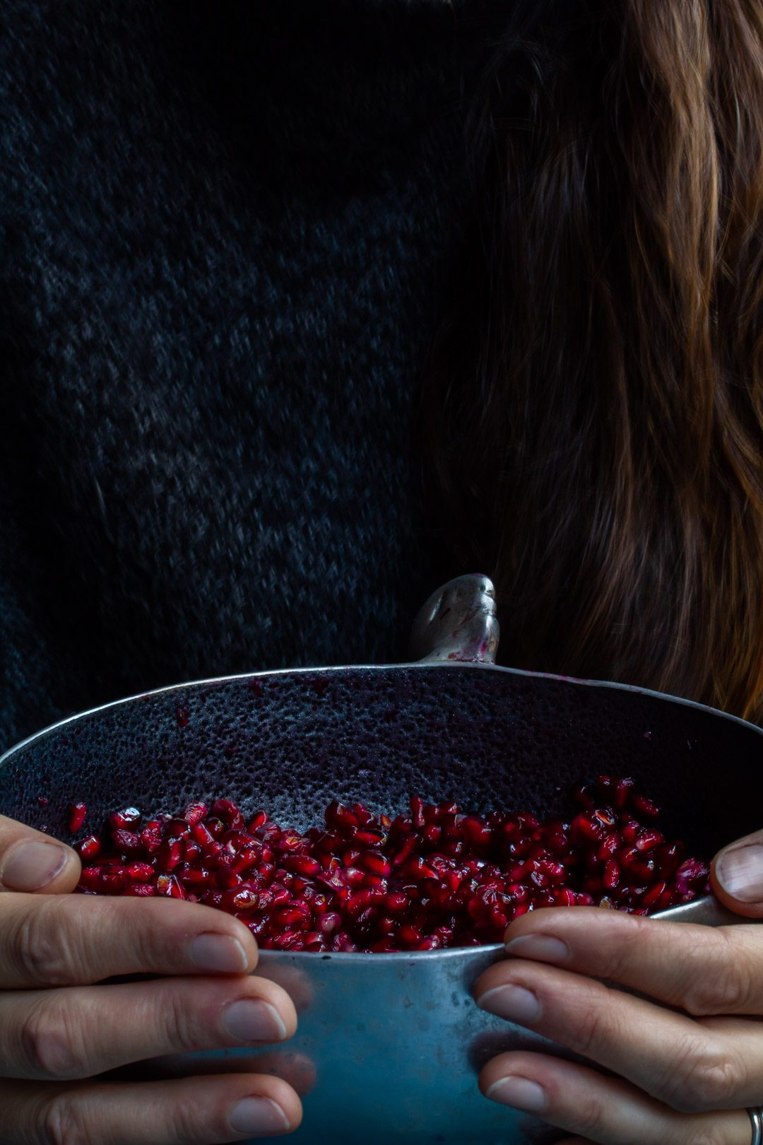 hands holding a metal bowl of pomegranate arils used to make grenadine