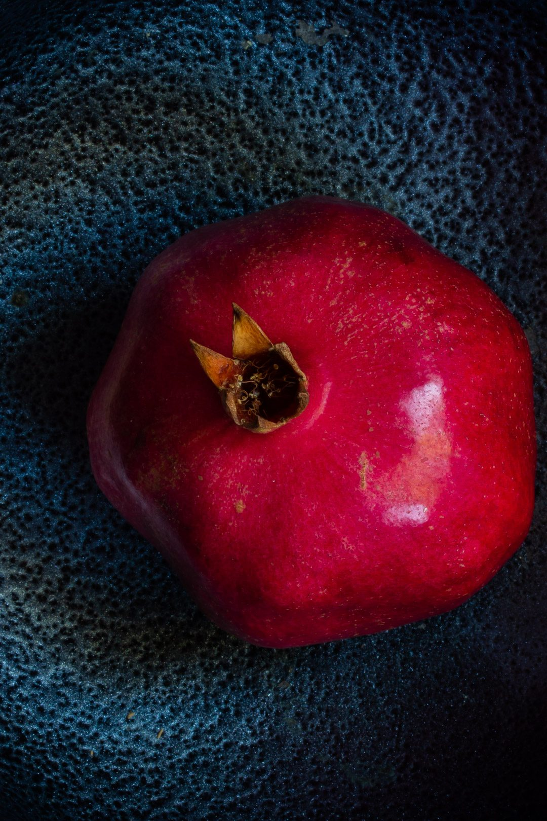 pomegranate on black textured background form above used to make grenadine
