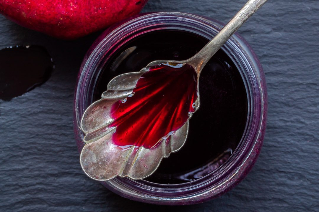 pomegranate molasses with vintage spoon used to make grenadine